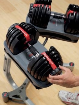 a guy adjusts a bowflex dumbbell that's sitting on a rack