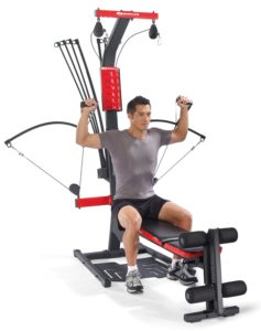 a man does a shoulder press on his new bowflex home gym