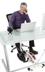 a guy uses an elliptical while sitting at his desk