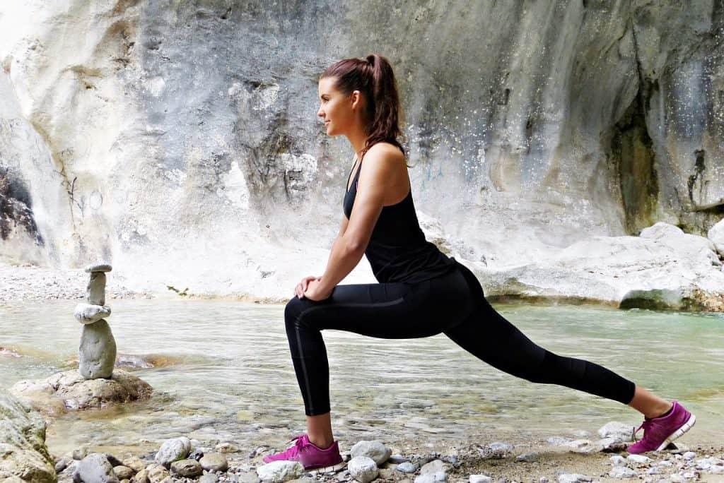 a woman stretches near a river