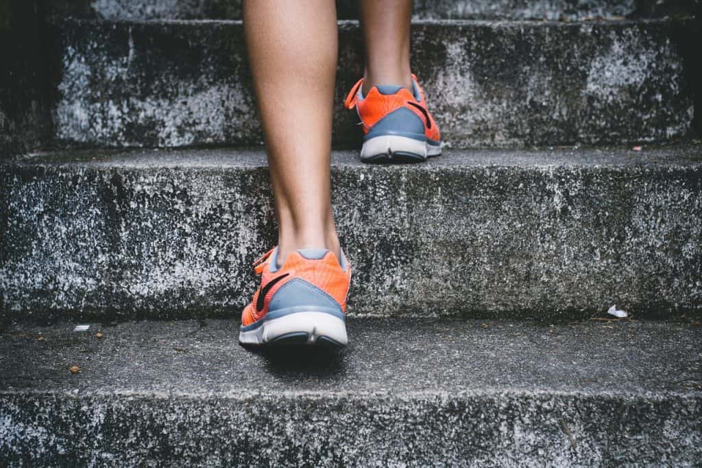 a woman walks up the park steps in sports shoes