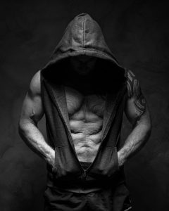 very fit older man stands with hood on head and sweatshirt open exposing his abs