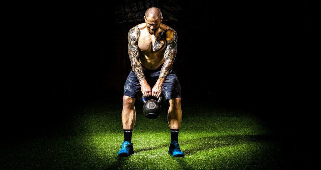an extremely fit older man prepares to swing a kettle bell