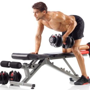 a fitness model uses the bowflex adjustable dumbbells and bench