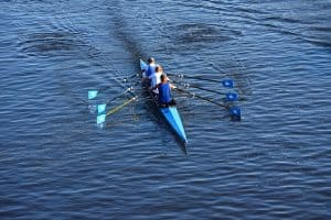 a group of men do a rowing workout on the water