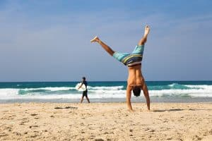 a guy does a summersault on the beach