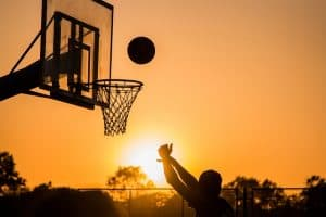 a guy shoots a basketball into the sunset