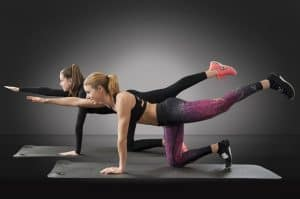 two women do the bird dog workout for lower back pain