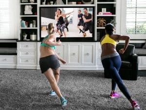 two women do a daily burn fitness workout in their living room