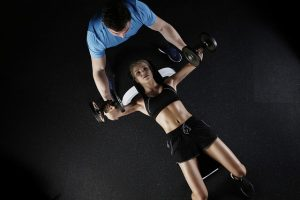 a woman bench presses with a coach