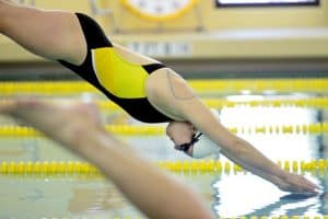 a swimmer dives in to swim some laps