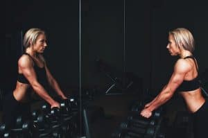 a woman grabs some dumbbells to do a chest press