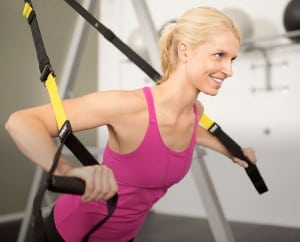 a woman uses the TRX for a chest workout