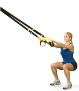 a woman does squats using the TRX