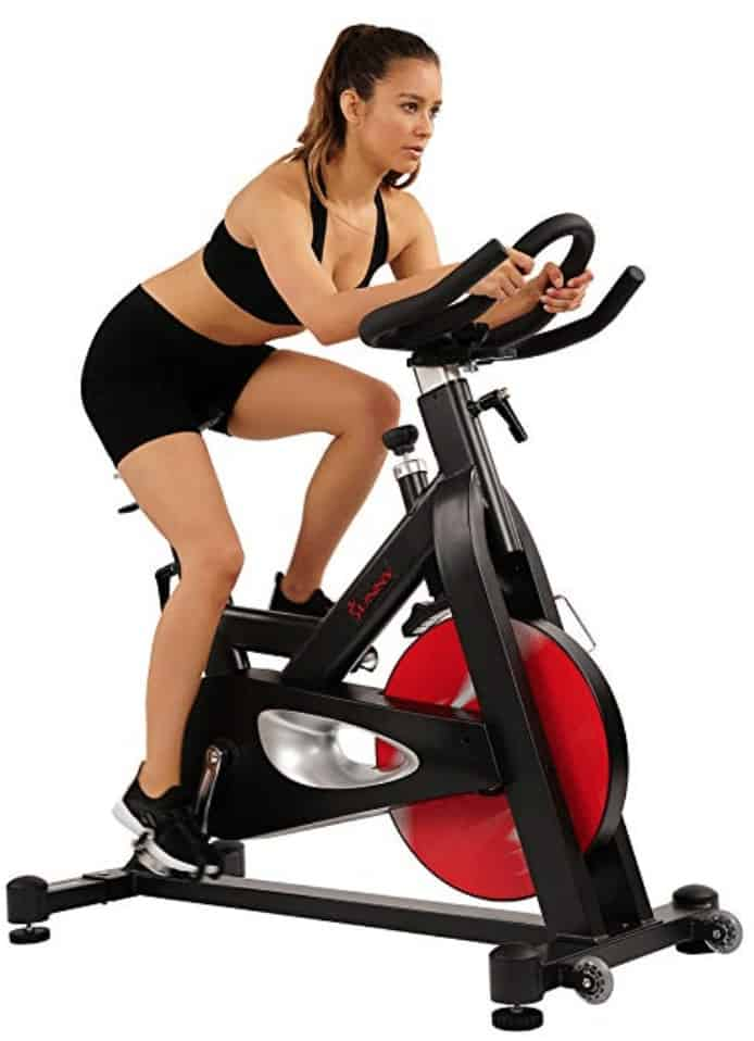 a woman rides the Sunny Health & Fitness Evolution Pro
