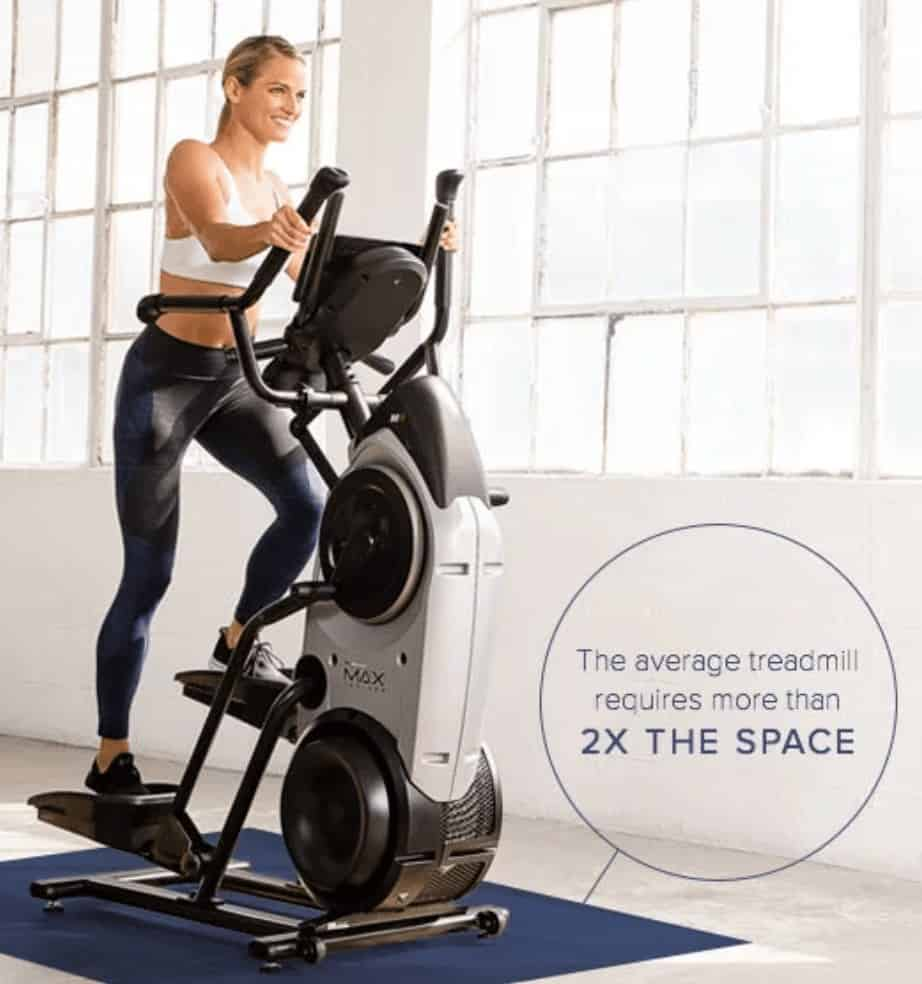 a woman rides the max trainer while showing its space saving design