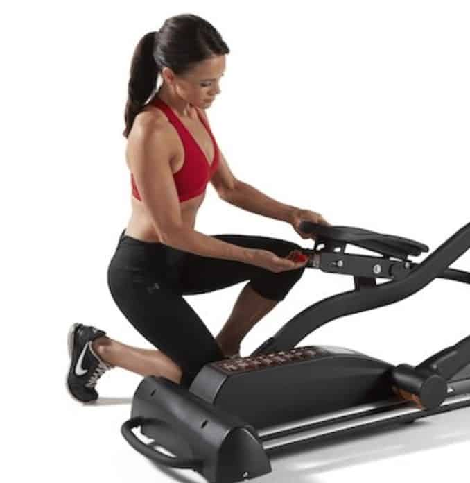 a woman check the pedals on her elliptical
