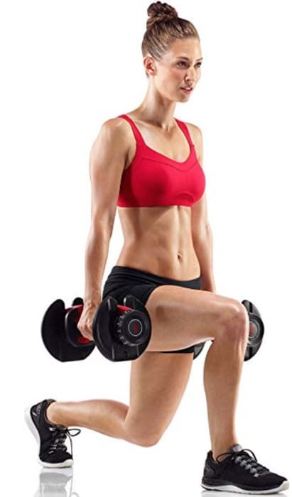 a woman does split squats with her bowflex dumbbells