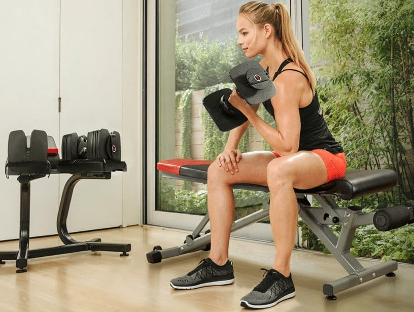 a woman working out with the bowflex selecttech dumbbells