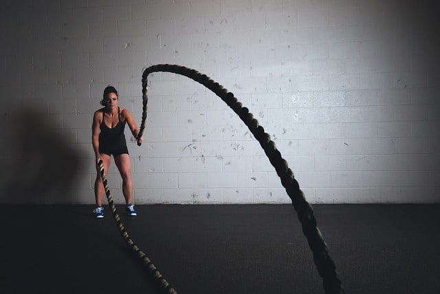 a woman uses battle ropes as part of her HIIT training