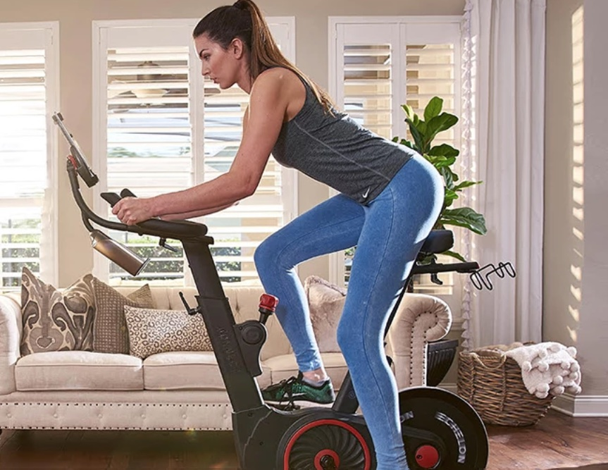 a woman rides a discounted spin bike that she bought on black friday