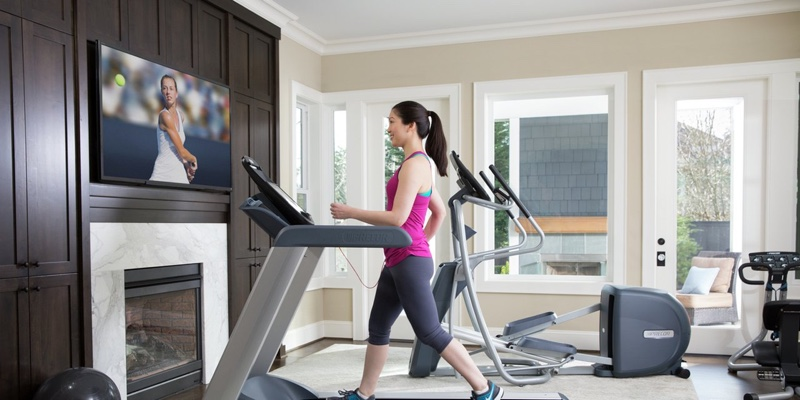 a woman uses precor equipment in her home gym